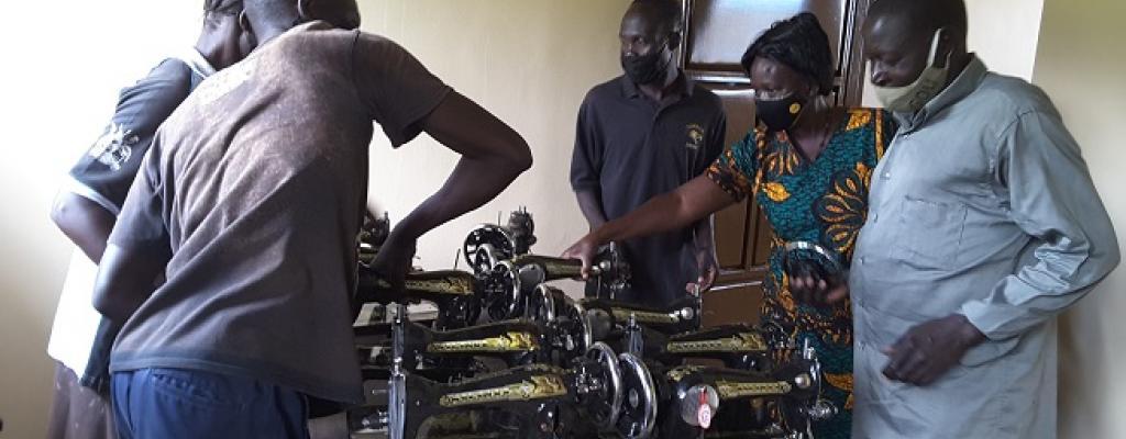 Amuru DEO, Ms Joyce Lanyero handing over sewing machines to SMC members of St. Philip Teddi primary school